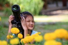Children take photo of yellow flower by dslr camera in the garde Royalty Free Stock Photo