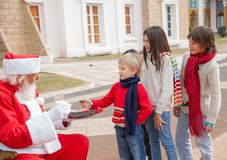 Children Taking Biscuits From Santa Claus Stock Photo