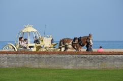 Children taking cinderella carriage ride by Great Yarmouth seafront. Great Yarmouth  Norfolk  , United Kingdom - October 25, 2016: Children taking cinderella Royalty Free Stock Photography