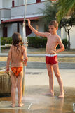Children are taking outdoor shower after swim. Little brother and sister are taking outdoor shower after swim, focus on boy Royalty Free Stock Photography