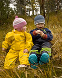 Children talking. Two small children (2 and 3 years old) sitting outside in an autumn forest, talking Stock Photography