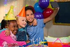 Children talking selfie through mobile phone Royalty Free Stock Image