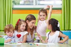Children talking to nursery teacher. In kindergarten while painting pictures Stock Images