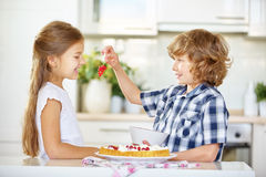 Children tasting red currants while baking Stock Photos