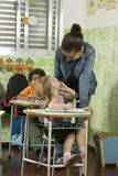 Children With Teacher. Children with their teacher in a classroom.  They are smiling. Vertically framed shot Stock Photo