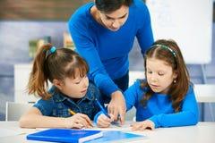 Children and teacher in classroom. Elementary age children listening to female teacher in school classroom Stock Images