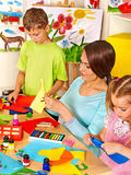 Children with teacher at classroom. Stock Photo