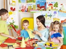 Children with teacher at classroom. Happy children  with scissors at classroom Stock Photo