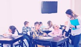 Children with teacher in classroom. Little children with teacher in school Stock Photo