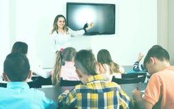 Children with teacher in classroom. Little children working with teacher in classroom Stock Image