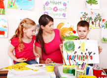 Children with teacher draw paints in classroom. Stock Photos