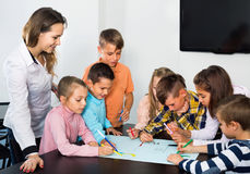 Children with teacher drawing together in classroom. Little children with teacher drawing together in classroom Stock Images