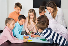 Children with teacher drawing together in classroom. Little cheerful smiling children with teacher drawing together in classroom Royalty Free Stock Photos