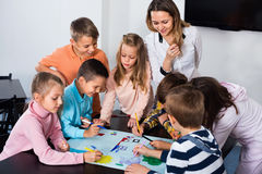 Children with teacher drawing together in classroom Stock Image