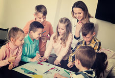 Children with teacher drawing together in classroom. Little smiling children with teacher drawing together in classroom Royalty Free Stock Image