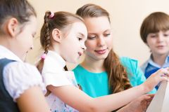 Children with the teacher engaged in painting stock photography