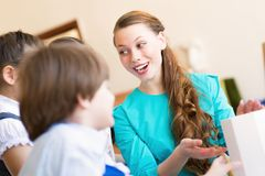 Children with the teacher engaged in painting royalty free stock image
