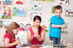Children and teacher mould from clay in play room. Royalty Free Stock Photography