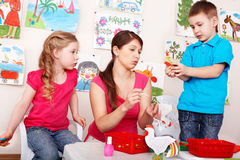 Children  with teacher  in play room. Stock Photo