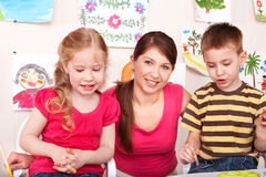 Children with teacher in play room. Stock Image