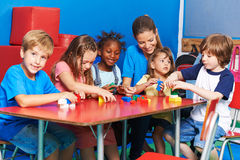 Children an teacher playing with building blocks. Together in preschool stock photo