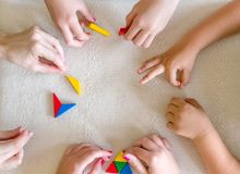 Children and Teacher playing Tangram together. royalty free stock photo