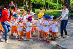 Children and teacher playing in the zoo Royalty Free Stock Images