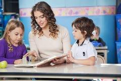 Children And Teacher Reading Book In Preschool stock photo