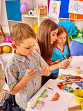 Children with teacher woman painting on paper in kindergarten . Stock Photo