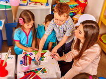 Children with teacher woman painting on paper in kindergarten . Royalty Free Stock Image