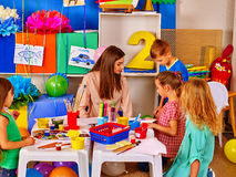 Children with teacher woman painting on paper in kindergarten . Stock Photography