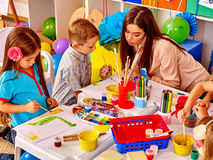Children with teacher woman painting on paper in Royalty Free Stock Photos