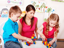 Children and teacher with wood block in preschool. Stock Images