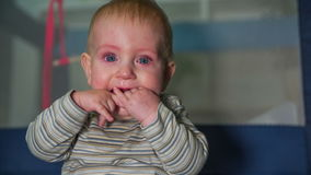 Children with tears in his eyes. Small blue eyes baby boy with tears in his eyes and putting hi hands in his mouth the footage is recorded in slow motion in stock video footage