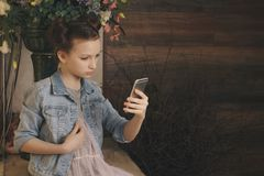 Single sad teen holding a mobile phone lamenting sitting on the bed in her bedroom with a dark light in the background. Children, technology and communication Stock Photo