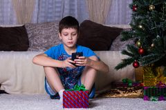 children, technology, internet communication and people concept - boy with smartphone texting message or playing game at home, New royalty free stock photography