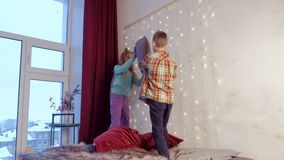 Children teen boy and girl fighting pillows in bedroom on Christmas holidays. Children teen boy and girl playing fighting pillows together in bedroom with big stock video footage
