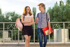 Children teenagers with backpacks, textbooks, notebooks go to school, back to school. Children teenagers with backpacks, textbooks, notebooks go to school, back stock photography
