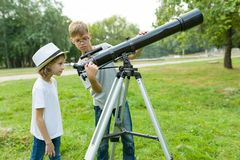 Children teenagers in the park looking through a telescope.  royalty free stock images