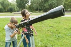 Children teenagers in the park looking through a telescope.  royalty free stock image