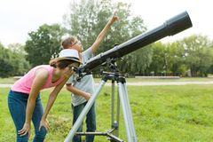 Children teenagers in the park looking through a telescope stock image