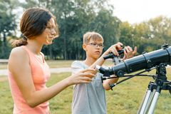 Children teenagers with telescope look at the sky in nature.  royalty free stock photos
