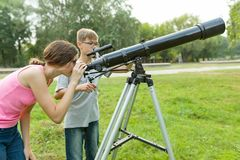 Children teenagers with telescope look at the sky in nature.  stock photo