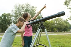 Children teenagers with telescope look at the sky in nature.  royalty free stock photo