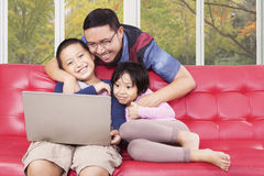 Children and their dad using laptop at home Royalty Free Stock Photo
