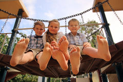 Children with their feet in the air. Sitting on a bridge royalty free stock photo