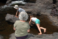 Children and their grandmother playing in the brook. Children with their grandmother playing and climbing the rocks in a country brook getting wet in the water Royalty Free Stock Photos