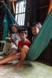 Children in their house in a Cambodian fishing village. SIHANOUKVILLE, CAMBODIA - 7/20/2015: Three children sit in a hammock inside their home in a rural fishing Stock Photography