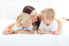 Children and their mom discussing lying on a bed royalty free stock image