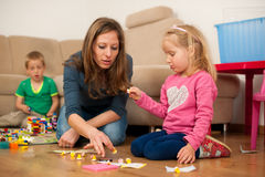 Children and their mother are playing with blocks on the ground Stock Image